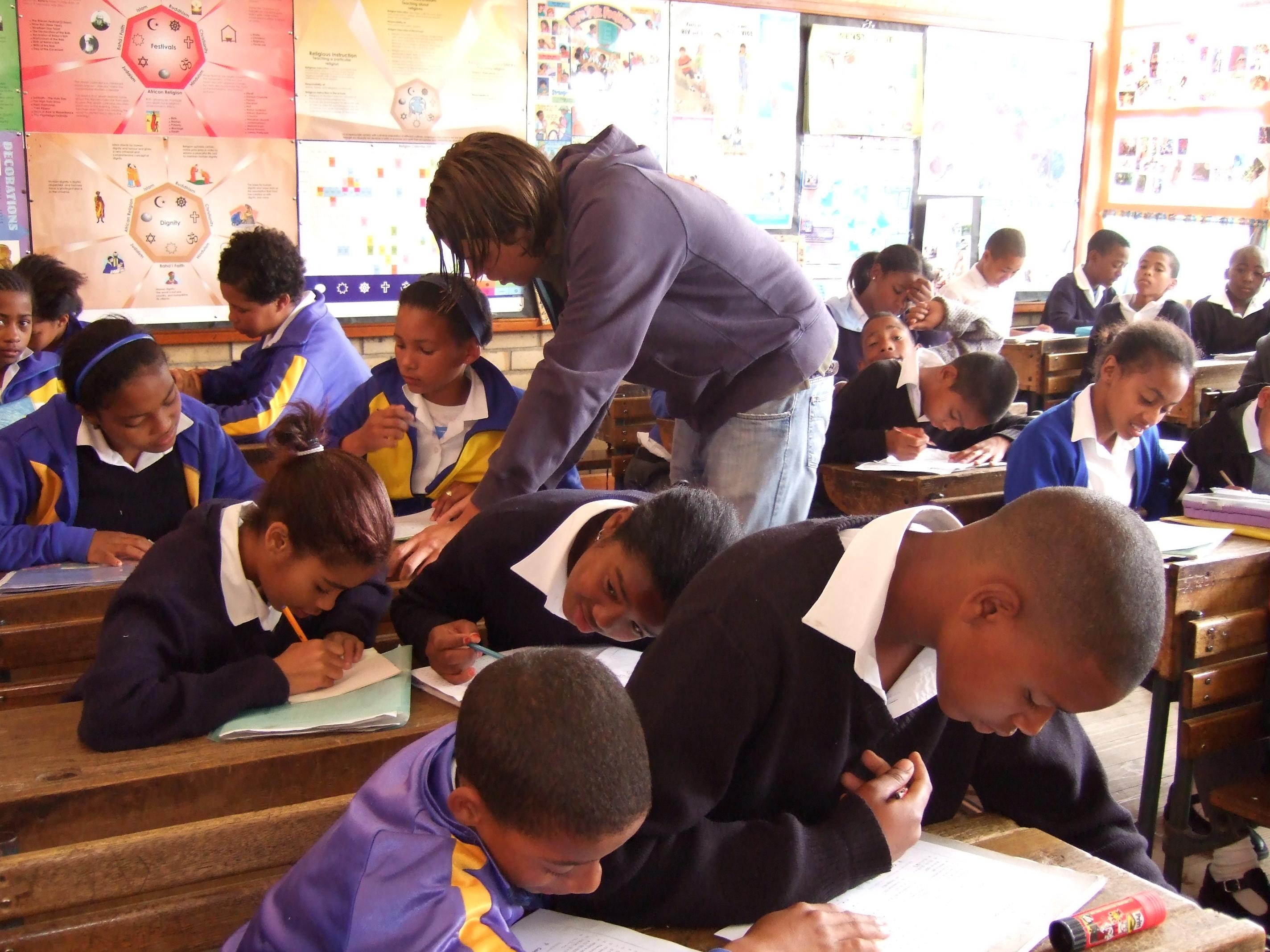 Students complete their classroom exercise while a volunteer assists during her teaching work experience in South Africa